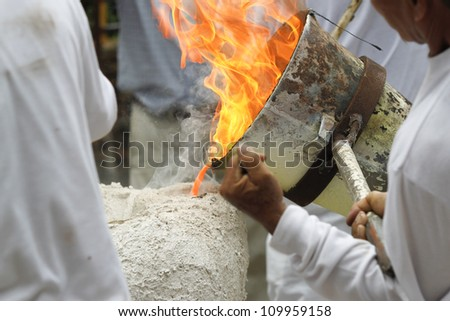 ancient metal cast process for buddha statue ,pouring liquid metal into mold - stock photo