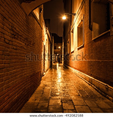 Ancient narrow streets and facades of old medieval buildings at night time close-up. Venice, Italy.