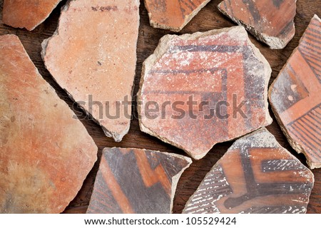 ancient Native American Indian (Anasazi) artifacts, several pottery fragments  on a wood background - stock photo