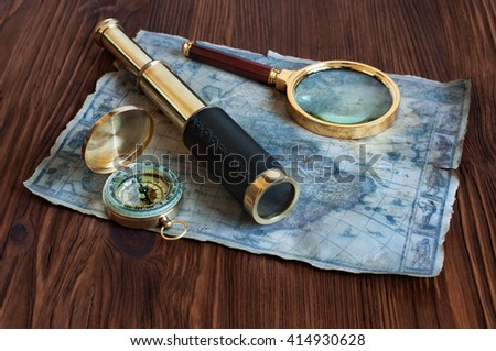 Ancient nautical instruments: a telescope, map, compass and magnifying glass on a wooden table