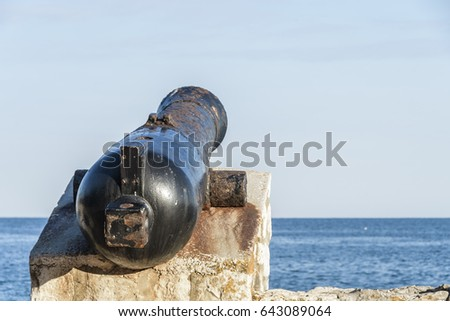 Ancient old cannon on coastal fortress walls, aiming to the sea; coastal fortress defense