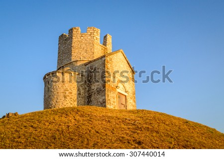 Ancient old croatian style church of St Nicholas near Nin and Zadar, Croatia, with a watch tower on the top, built on the top of a little hill. - stock photo