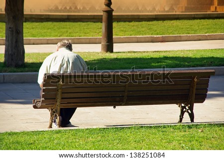 Ancient old man sitting on a bank of a public park - stock photo