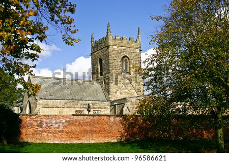 ancient old rural stone church with a stone wall infront and trees in the foreground on a warm summer day - stock photo