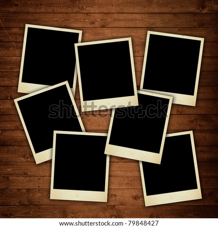 ancient photo frames on wooden texture - stock photo