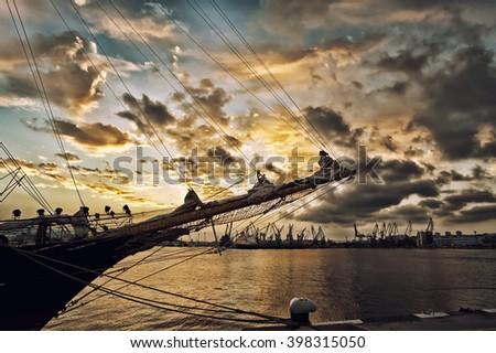 Ancient pirate ship sailing at sunset. - stock photo