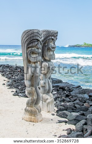 Ancient Polynesian style tiki wooden carvings greet visitors to Ki'i Pu'uhonua O Honaunau National Park on the Big Island of Hawaii. - stock photo