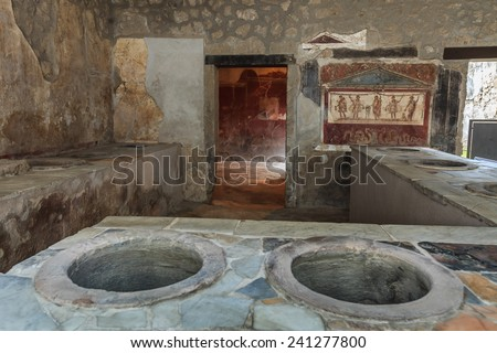 Ancient Pompeii - Thermopolium of Asellina with old food serving counter - stock photo