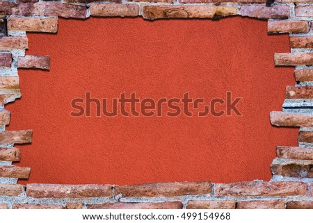 Ancient red brick wall with a hole over a background red.