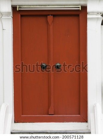 Ancient red carving wooden door of Thai temple in Bangkok, Thailand. - stock photo