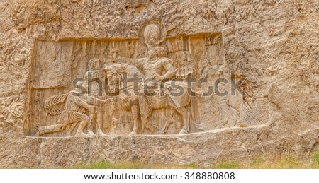 Ancient relief of the necropolis Naqsh-e Rustam that shows the triumph of Shapur I over the Roman Emperor Valerian and Philip the Arab. - stock photo