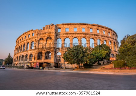 Ancient Roman Amphitheater in Pula, Croatia, Famous Travel Destination, in Sunny Summer Evening with Trees and Flowers in Foreground - stock photo