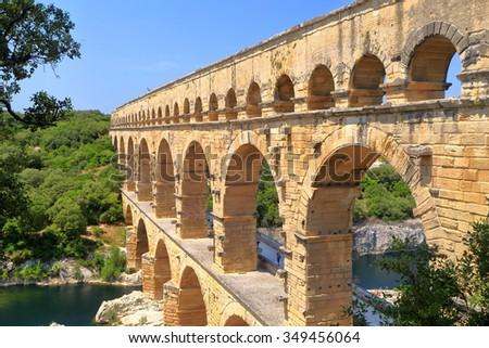 Ancient Roman aqueduct of Pont du Gard surrounded by vegetation near Nimes, France - stock photo
