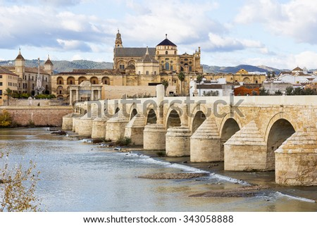 Ancient Roman Bridge across the river Guadalquivir in Cordoba. Cordoba Mosque and Cathedral is in the background.