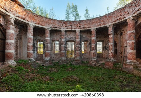 Ancient rotunda with columns without a dome. Abandoned brick temple overgrown with grass - stock photo