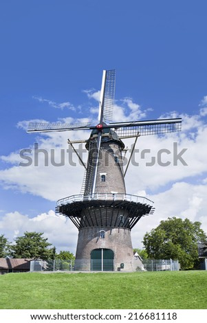 Ancient round brick floor mill in a green field with a blue sky and dramatic clouds.  - stock photo