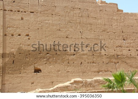 Ancient ruins of Karnak temple, wall with images of pharaohs and gods, Luxor, Thebes, Egypt - stock photo