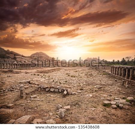Ancient ruins of Vijayanagara Empire at dramatic sky in Hampi, Karnataka, India - stock photo