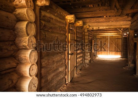 Ancient rural Russian interior, corridor with walls made of rough logs and glowing end