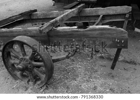 Ancient rusted and rotted farm equipment is a victim of time (monochrome image).