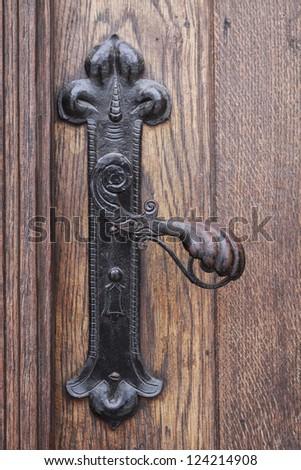 Ancient rusty church door handle on brown old wooden door - stock photo