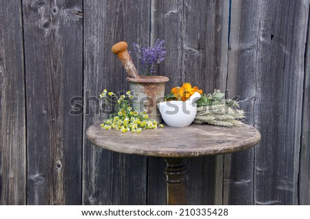 ancient rusty iron mortar and various medical herbs on old wooden table - stock photo