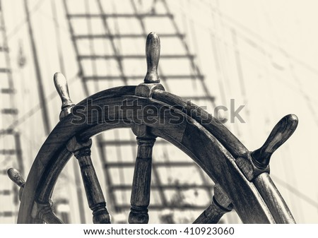 Ancient ship with captain wheel in retro style. Steering wheel on the old sailboat. Sea voyage on the sailing vessel. Travel on the wooden tall ship, skipper steering wheel in front view. - stock photo