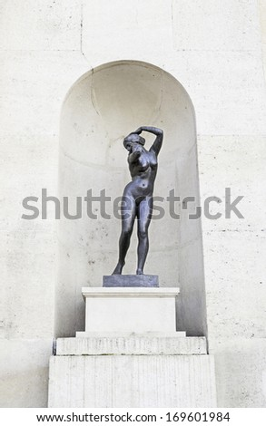 Ancient statue in the city, detail of an ancient statue on the facade of an old house - stock photo