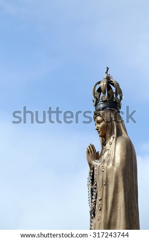 ancient statue of our Lady with clasped hands and the precious Crown