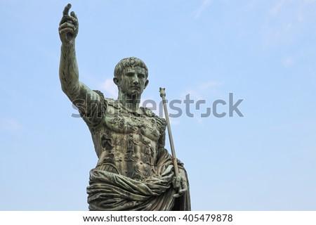 Ancient statue over blue sky. S.P.Q.R. IMP CAESAR Augustus PATRIAE PATER. Via dei Fori Imperiali street, Rome, Italy - stock photo