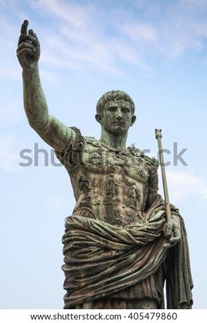 Ancient statue S.P.Q.R. IMP CAESAR Augustus PATRIAE PATER over cloudy sky. Via dei Fori Imperiali street, Rome, Italy - stock photo