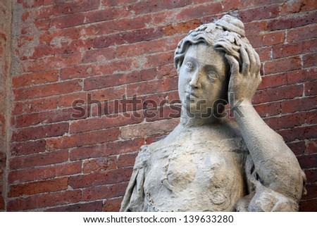 ancient statue with headaches and the brick wall - stock photo