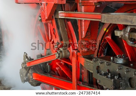 Ancient steam locomotive in steam. Live steam around mechanical parts, wheels and equipment of the train., - stock photo