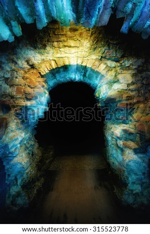 Ancient stone arch illuminated with blue and yellow light to create a magical and mysterious gateway into the dark - stock photo