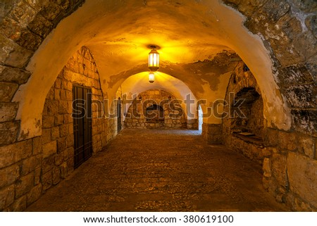 Ancient stone arched passage illuminated with lanterns in Old City of Jerusalem, Israel. - stock photo