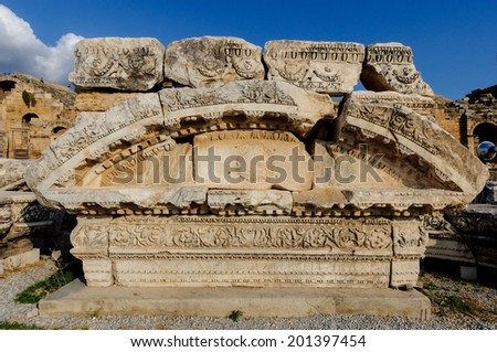 Ancient stone carving of an arch for a doorway at Hierapolis. - stock photo