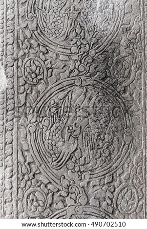 Ancient stone carving on a wall with traditional Cambodian Khmer floral and birds decorative pattern ornament