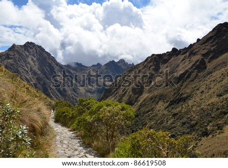 Ancient Stone Inca Trail Path in the Andes Leading to Machu Picchu With Cloudy Sky in the Background - stock photo
