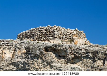 Ancient stone talayot at the cliff of the south coast of Menorca island, Spain. - stock photo