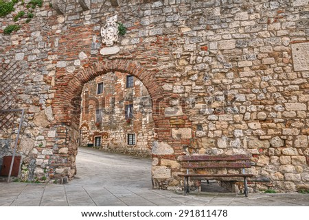 ancient stone wall with entrance gate in the medieval village Rosignano Marittimo, Leghorn, Tuscany, Italy