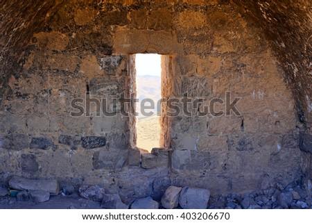 Ancient stone window in Judean desert - stock photo
