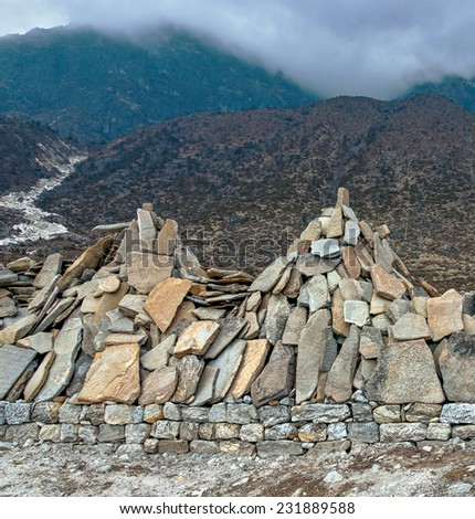 Ancient stones carved with the buddhist mantras near great stupa in Khunde - Nepal, Himalayas - stock photo