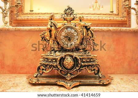 Ancient style clock on the marble table. - stock photo