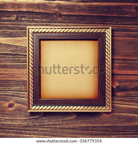 ancient style golden photo image frame on wood background - stock photo