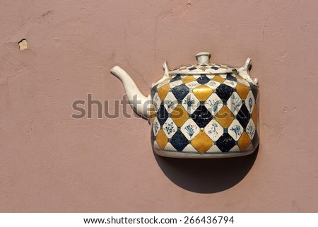 Ancient teapot embedded in facade of old building in Vilnius, Lithuania. - stock photo