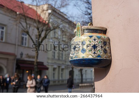 Ancient teapot embedded in facade of old building in Vilnius, Lithuania. Inscription on the teapot is address of this building - Bernardine street 2. - stock photo