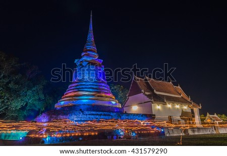 Ancient temple walking with lighted candles in hand around a temple candles light trail of Buddhism Ceremony at old pagoda in Sokothai Thailand with long exposure and low exposure - stock photo