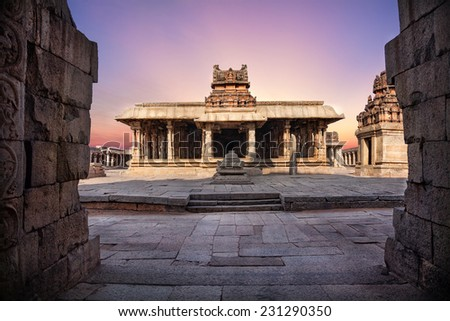 Ancient temple with columns at violet sky in Hampi, Karnataka, India - stock photo