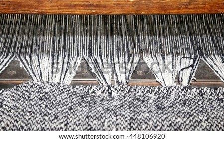 ancient textile loom of wood with black and white color woolen threads for the production of woolen blankets - stock photo