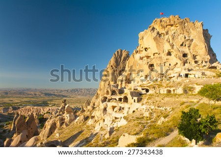 Ancient town and a castle of Uchisar dug from a mountains after sunrise, Cappadocia, Turkey - stock photo